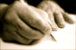 Old hands writing something with a pen in a notebook