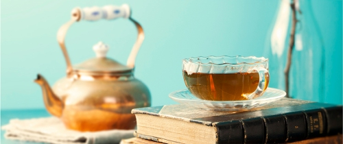 Cup of tea with teapot and vintage books on wooden table Blue background